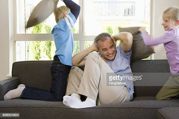 Children playing pillow fight with father at home