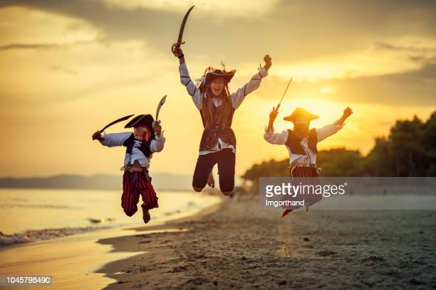 children playing pirates on beach - female pirate stock photos and pictures
