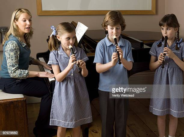 children playing recorders in school - recorder musical instrument stock photos and pictures