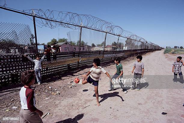 Children Playing Soccer Along Border Fence