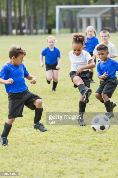children playing soccer, competing for ball - match sport stock pictures, royalty-free photos & images