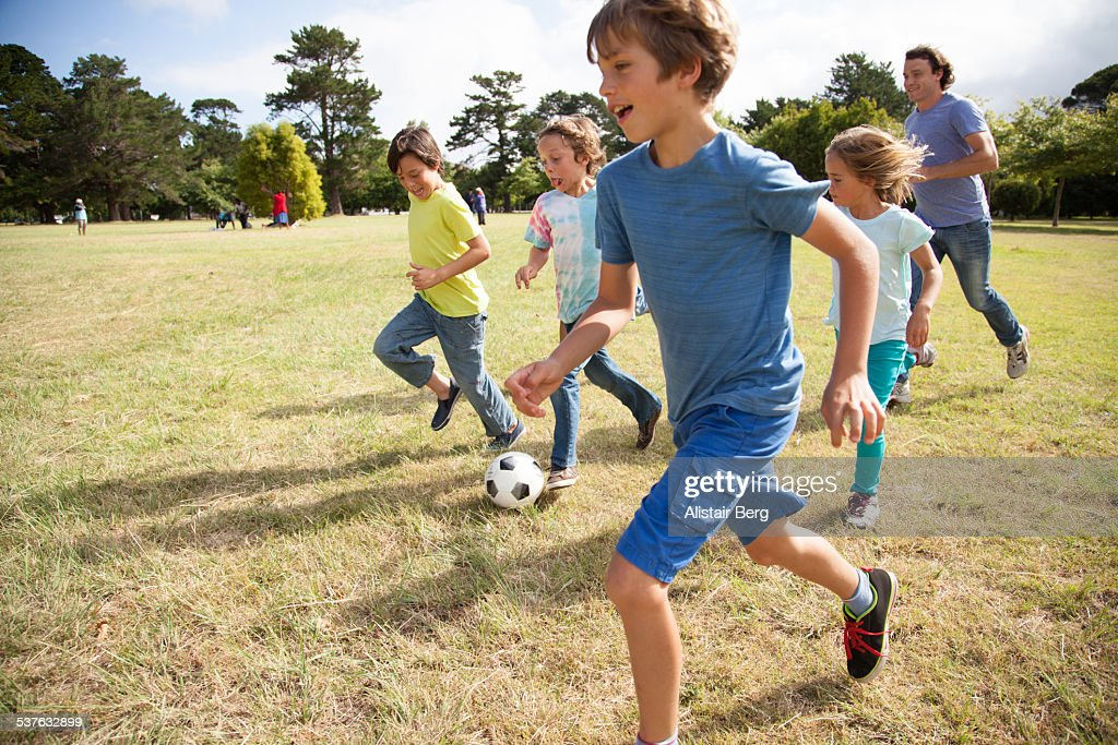 Children playing soccer in park : Foto de stock
