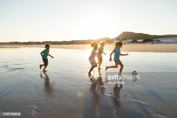 children playing soccer on a beach at sunset - nur kinder stock-fotos und bilder