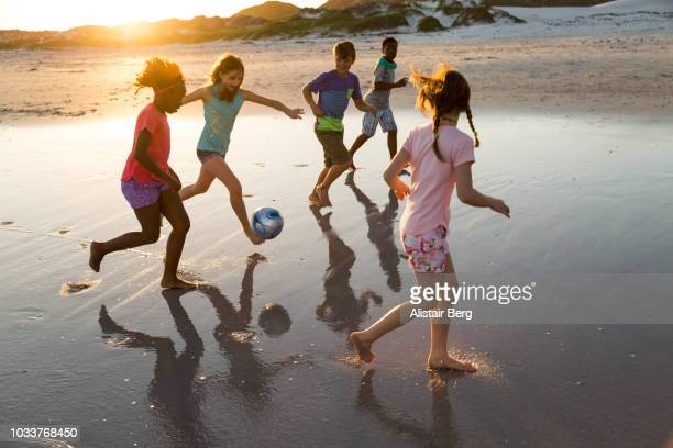 children playing soccer on a beach at sunset - sporting term stock pictures, royalty-free photos & images
