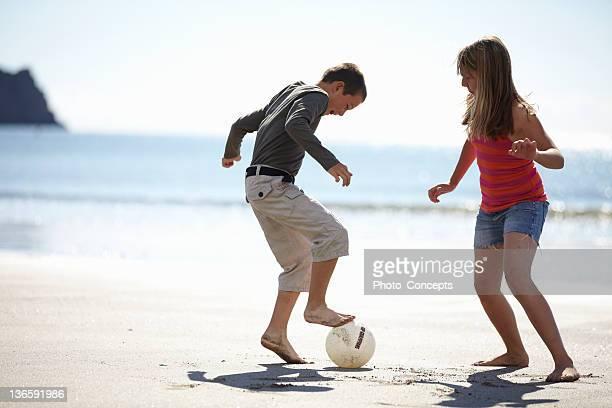 Niños jugando al fútbol en la playa