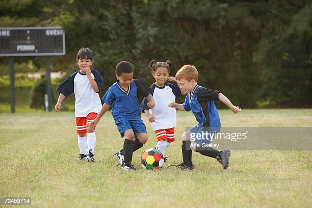 children playing soccer outdoors - sporting term stock-fotos und bilder