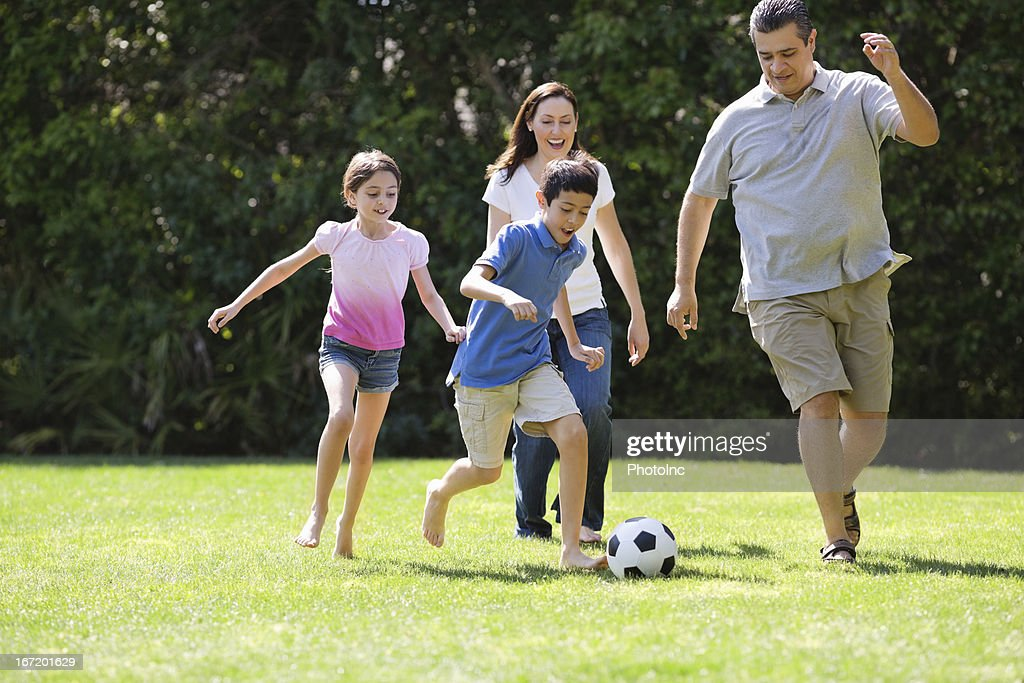 Children Playing Soccer With Parents : Stock Photo