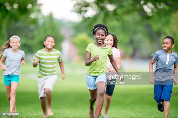 children playing tag at the park - kids playing tag stock photos and pictures