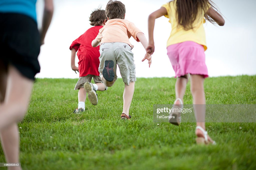 Children Playing Tag While Running Up a Hill : Stock Photo