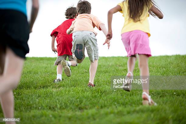 Children Playing Tag While Running Up a Hill