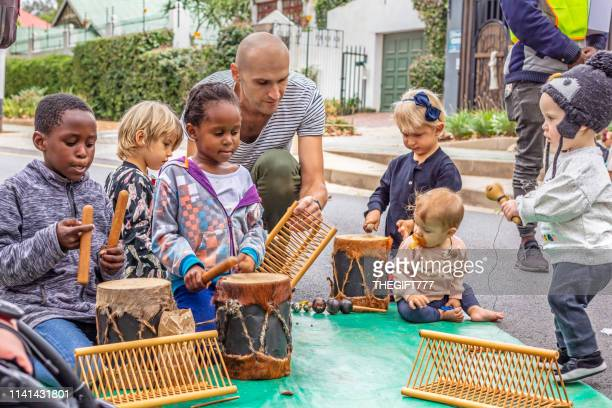 children playing the drums with parent overlooking - gauteng province stock pictures, royalty-free photos & images
