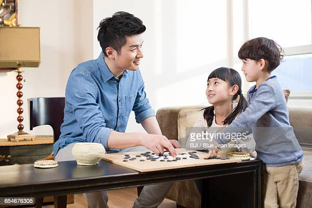 Children playing the game of Go with father