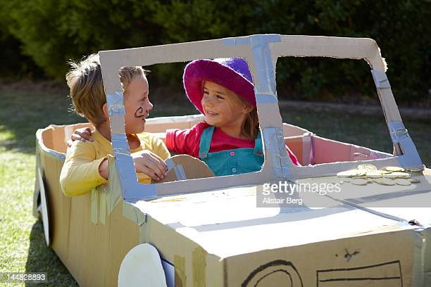 Children playing together in a cardboard car