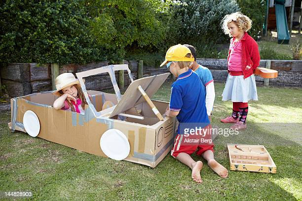 Children playing together with a cardboard car