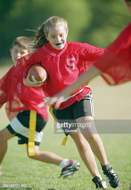Children (9-11) playing touch football (blurred motion)