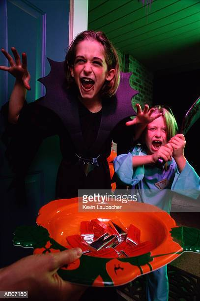 Children (6-12) playing 'trick or treat' at front door
