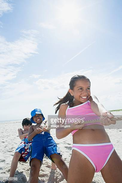 children playing tug of war - little girl swimsuit stock photos and pictures