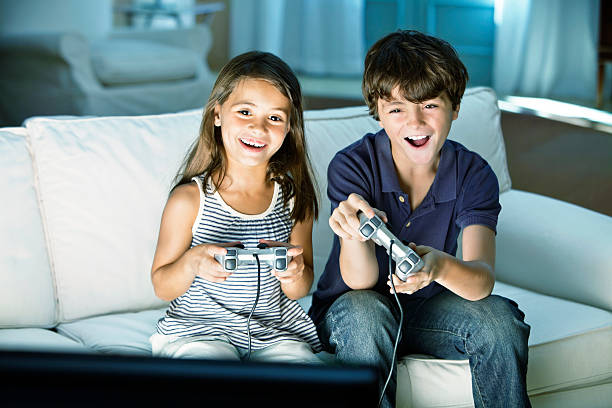 Children playing video game at home