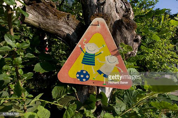 A children playing warning sign in a rural location in northern Italy The cartoon qualities of the children smiling while playing with their ball is...