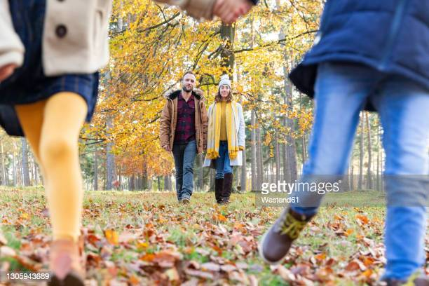 children playing while running with parents walking in background at forest - focus on background stock pictures, royalty-free photos & images