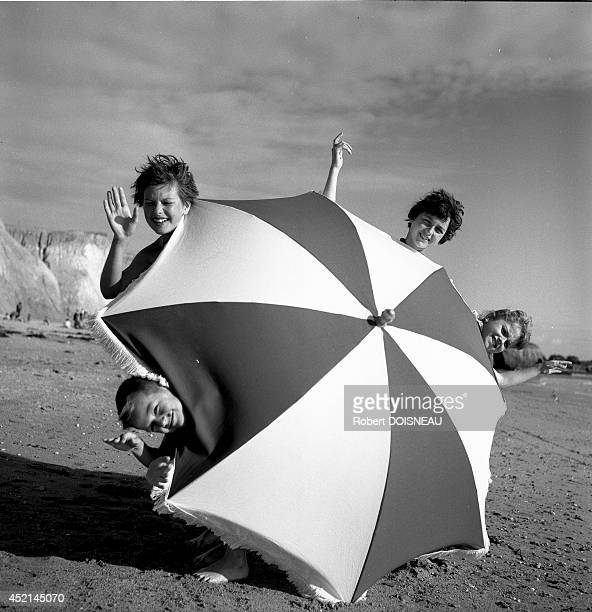 Children playing with a beach umbrella at the 'Plage de la mine d'or' 1956 in Penestin France