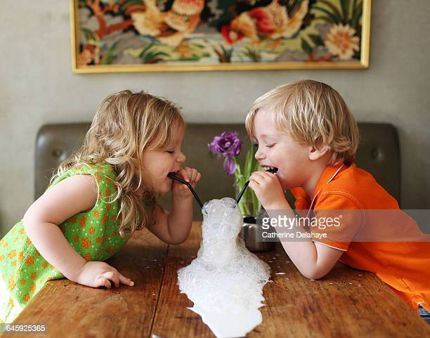 2 children playing with a glass of milk