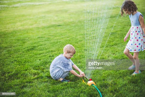 Children playing with a lawn sprinkler