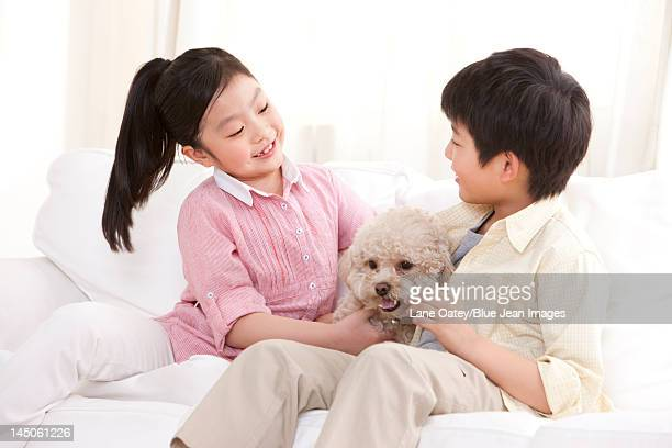 Children playing with a pet toy poodle