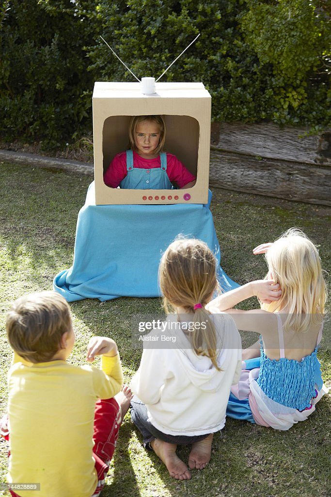 Children playing with a pretend television : Stock Photo