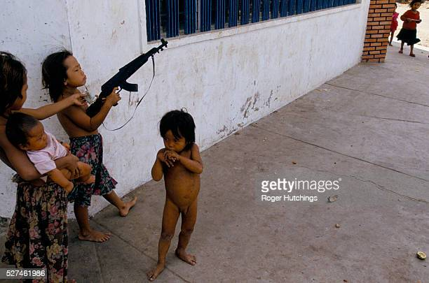 Children playing with an imitation gun in Phnom Penh