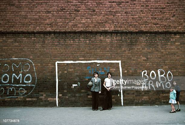 Children playing with an improvised goalpost painted on a brick wall in Manchester England in 1976