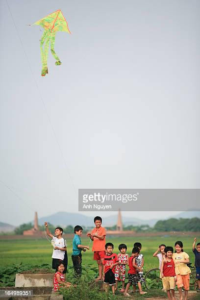 Children playing with and flying kites as a daily activity in the afternoon in warm months of the year in the countryside of North Vietnam,...