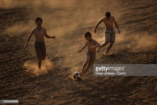 Children Playing With Ball On Sand