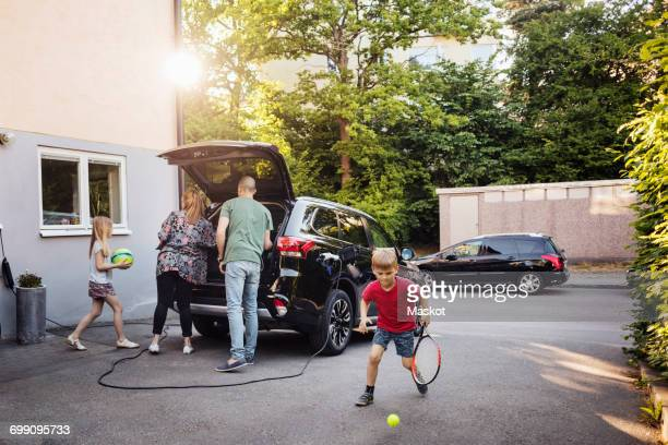 Children playing with balls while parents loading car trunk in back yard