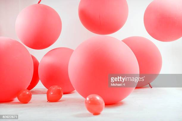 Children playing with big red ballons