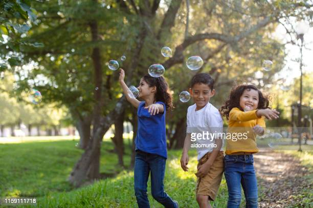 children playing with bubbles outdoors - children only stock pictures, royalty-free photos & images