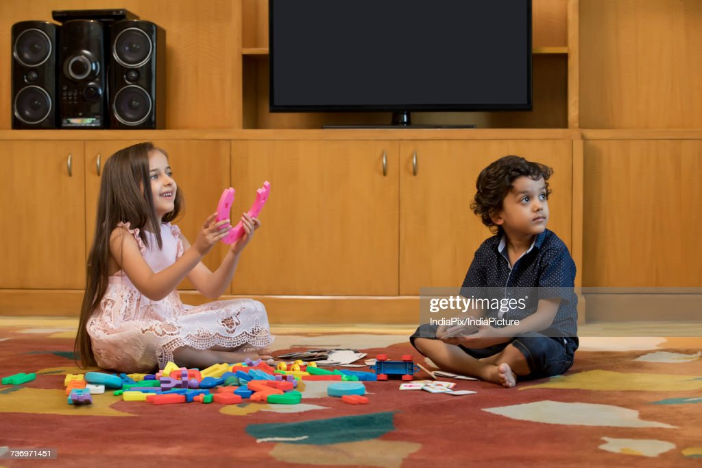 Children playing with building block in living room : Stock-Foto