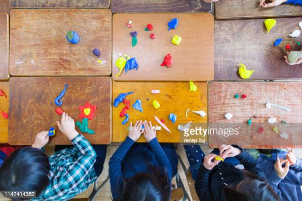 children playing with clay in classroom - preschool stock pictures, royalty-free photos & images