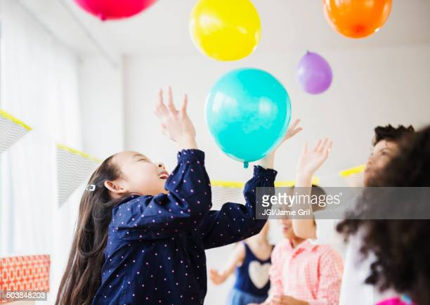 Children playing with colorful balloons at party