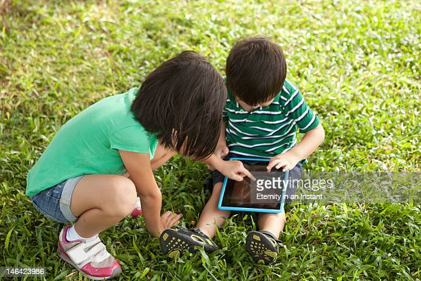 children playing with digital tablet device - newtechnology stock pictures, royalty-free photos & images
