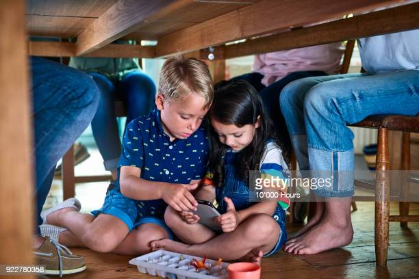 children playing with digital tablet under table - sotto foto e immagini stock