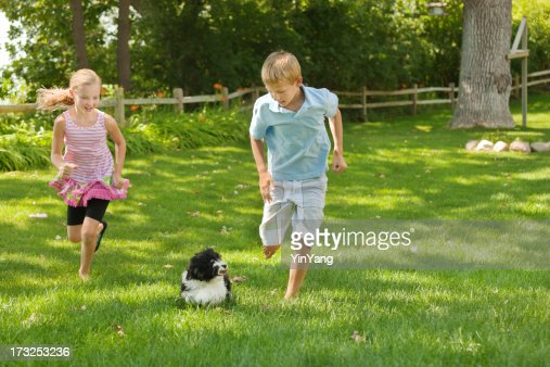 Children Playing With Family Pet Dog On The Grass Lawn
