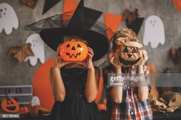 children playing with halloween decoration - halloween party stock photos and pictures