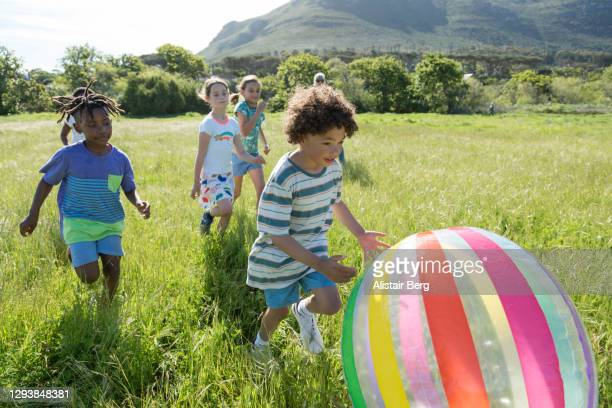 children playing with inflatable ball in a field - children only stock pictures, royalty-free photos & images