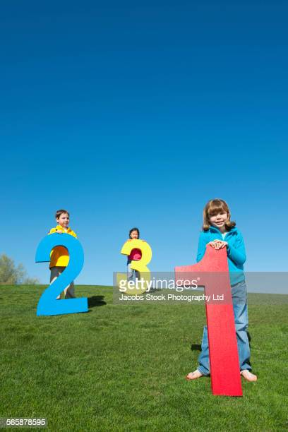 Children playing with large numbers in field