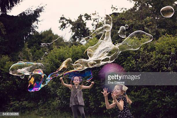 Children playing with large, spooky shaped bubbles