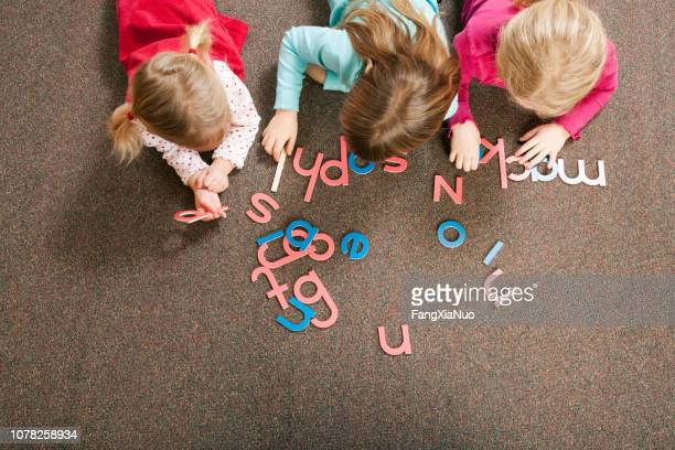 children playing with letter shapes in grade school classroom - spelling stock pictures, royalty-free photos & images