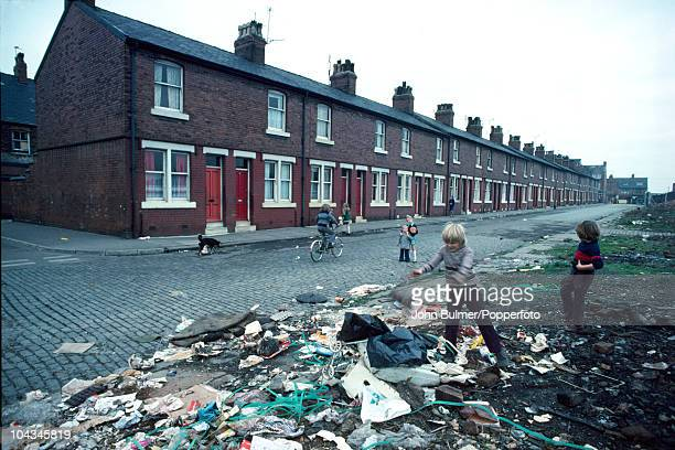 Children playing with litter on an area of waste ground in front of a row of terraced houses in Manchester England in 1976