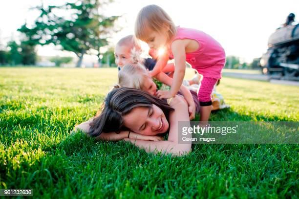 children playing with mother lying on grassy field at park - op de buik liggen stockfoto's en -beelden