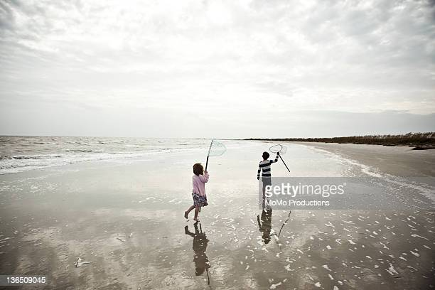 2 children playing with nets on beach
